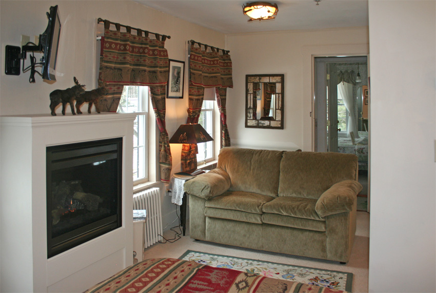 North Woods room- Queen bed with fireplace, TV and couch